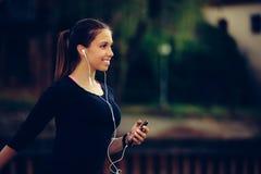 Ung kvinna som lyssnar till musik, medan vila, når att ha kört arkivbild