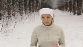 Ung kvinna som lyssnar till musik och joggar utanför i vinter lager videofilmer