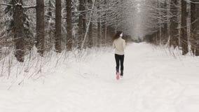 Ung kvinna som lyssnar till musik och joggar utanför i vinter arkivfilmer