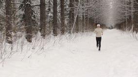 Ung kvinna som lyssnar till musik och joggar utanför i vinter stock video