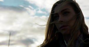 Ung kvinna som lyssnar till musik på hörlurar i en blåsiga centrala Stockholm lager videofilmer