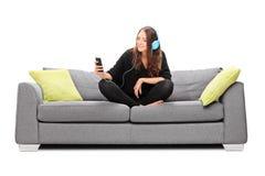 Ung kvinna som lyssnar till musik på hennes telefon Royaltyfria Bilder