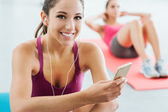 Ung kvinna som lyssnar till musik på idrottshallen fotografering för bildbyråer