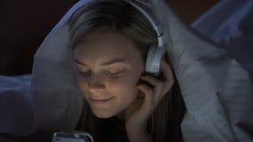 Ung kvinna som lyssnar till musik på natten lager videofilmer