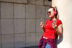 Ung kvinna som lyssnar till musik via hörlurar på gatan royaltyfria foton