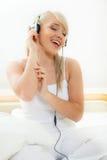 Ung kvinna som lyssnar till musiken Arkivfoto