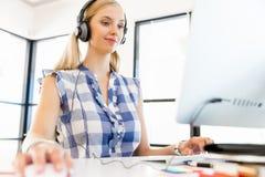 Ung kvinna som lyssnar till musiken, medan arbeta på en dator Arkivfoto