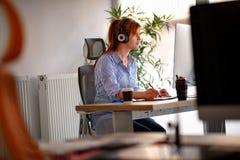 Ung kvinna som lyssnar till musiken, medan arbeta på en dator royaltyfri foto