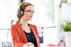 Ung kvinna som lyssnar till musiken, medan arbeta på en dator royaltyfria bilder