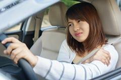 Ung kvinna som masserar hennes arm eller skuldra, medan köra en bil af arkivbild