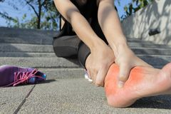Ung kvinna som masserar hennes smärtsamma fot från öva och körande sport- och övningsbegrepp royaltyfri foto