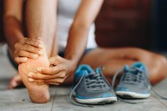 Ung kvinna som masserar hennes smärtsamma fot från att öva och runni arkivbild