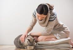 Ung kvinna som matar hennes katt Arkivfoto
