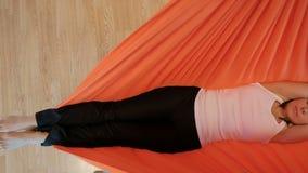 Ung kvinna som mediterar att ligga ner i hängmatta inomhus stock video