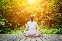 Ung kvinna som mediterar i en skogZen, meditation, sund andning Arkivfoton