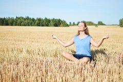 Ung kvinna som mediterar i fältet Arkivfoto