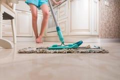 Ung kvinna som moppar kökgolvet fotografering för bildbyråer