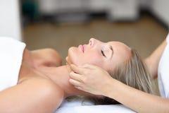 Ung kvinna som mottar en head massage i en brunnsortmitt arkivbilder
