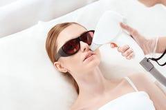 Ung kvinna som mottar epilation för laser-hårborttagning på framsida Arkivfoto