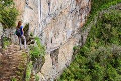 Ung kvinna som nära tycker om sikten av den Inca Bridge och klippabanan royaltyfri foto