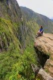 Ung kvinna som nära tycker om sikten av den Inca Bridge och klippabanan royaltyfri bild