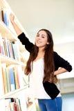 Ung kvinna som når för en bok royaltyfria bilder