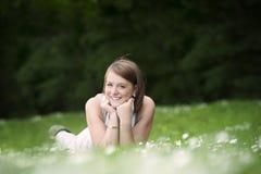 Ung kvinna som ner ligger i ett gräs med tusenskönor arkivbilder