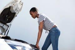 Ung kvinna som ner ser under huven av den brutna bilen på vägen Royaltyfria Foton