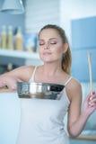Ung kvinna som njuter av lukten av hennes matlagning fotografering för bildbyråer