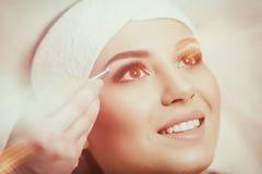 Ung kvinna som noppar hennes ögonbryn i skönhetsalong Royaltyfri Foto