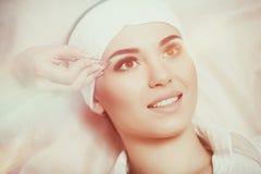 Ung kvinna som noppar hennes ögonbryn i skönhetsalong Royaltyfria Foton