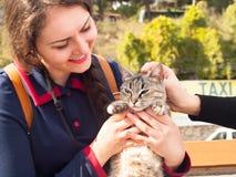 Ung kvinna som omfamnar och spelar med den fluffiga inhemska katten Fotografering för Bildbyråer