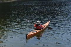Ung kvinna som paddlar i den alpina sjön fotografering för bildbyråer