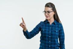 Ung kvinna som pekar hans finger på abstrakt ljus bakgrund som trycker på en digital knapp på en abstrakt skärm, faktisk manövere Fotografering för Bildbyråer