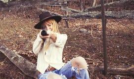 Ung kvinna som pekar vapnet på kameran Royaltyfria Bilder