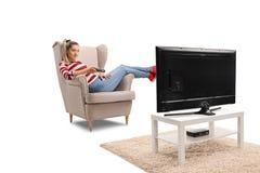 Ung kvinna som placeras i en hållande ögonen på television och changi för fåtölj arkivbild