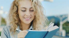 Ung kvinna som planerar hennes dag Han skriver anmärkningar, nöjt och lyckligt lager videofilmer
