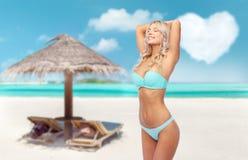 Ung kvinna som poserar i bikini på stranden royaltyfri fotografi