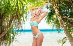 Ung kvinna som poserar i bikini på stranden arkivbild