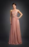 Ung kvinna som poserar i lyxig klänning arkivfoton
