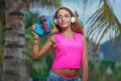 Ung kvinna som poserar med en skateboard Fotografering för Bildbyråer