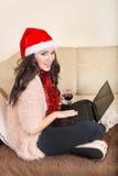 Ung kvinna som poserar med röda Santa Hat och rött vin Arkivfoton