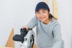 Ung kvinna som poserar, medan klippa trä Arkivfoto
