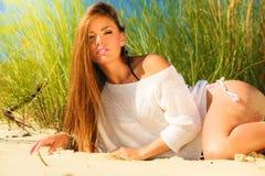 Ung kvinna som poserar på den gräs- dyn arkivfoto