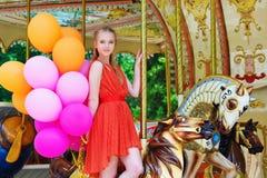 Ung kvinna som poserar på en karusell Arkivbild