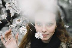 Ung kvinna som poserar p? gatan mot ett blomma tr?d royaltyfri fotografi