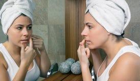 Ung kvinna som pressar en aknefinne i spegel Royaltyfria Foton