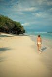 Ung kvinna som promenerar den tropiska stranden Arkivbilder