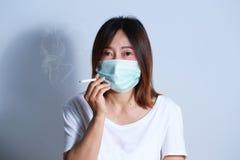 Ung kvinna som röker cigaretten med den skyddande maskeringen Arkivfoto