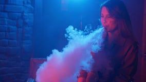 Ung kvinna som röker sprejflaskan i klubba på ett färgrikt ljus lager videofilmer